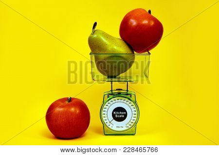 Ripe Red Apple, Pear And Kitchen Scales Close Up On A Yellow Background.