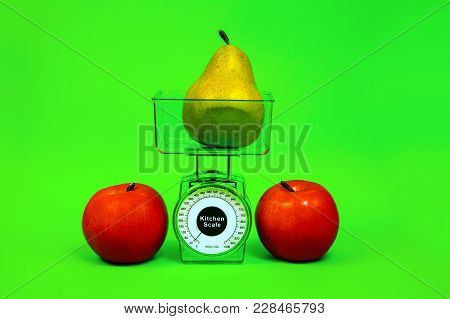 Ripe Red Apple, Pear And Kitchen Scales Close Up On A Green Background.