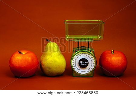 Ripe Red Apple, Pear And Kitchen Scales Close Up On A Brown Background.