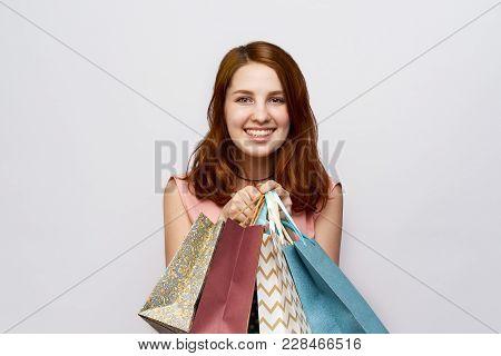 Photo Of Cheerful Joyful Girl With Snow-white Beautiful Smile On White Isolated Background Holding B