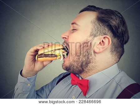 Side Profile Of A Fat Man Eating A Juicy Hamburger