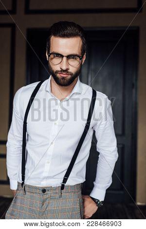 Fashionable Elegant Bearded Man Posing In Eyeglasses And Trendy Suspenders