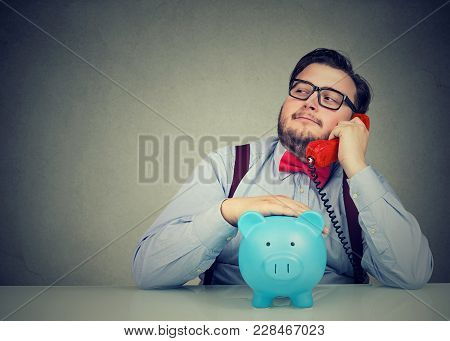 Confident Financial Advisor With Piggy Bank Callling On The Phone