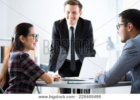 Businessmen recruit a young employee at the office
