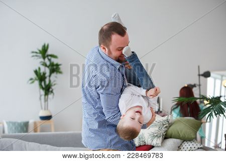 Family photo of man holding son in apartment