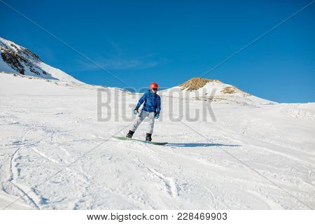 Image of sports man wearing blue jacket, helmet with snowboard riding on snowy slope
