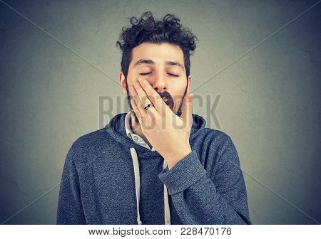 Young Hipster Man Yawning In Laziness Covering Mouth On Gray Background.