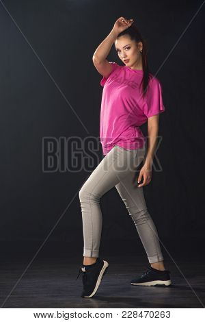 Young beautiful girl dancer dancing hip-hop on a black background