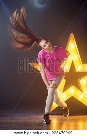 Young beautiful girl dancer dancing hip-hop on a star with lamp  background