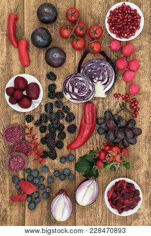Healthy food concept with fruit and vegetables of red, purple and blue colours very high in anthocyanins, vitamins, minerals and antioxidants on rustic oak background.