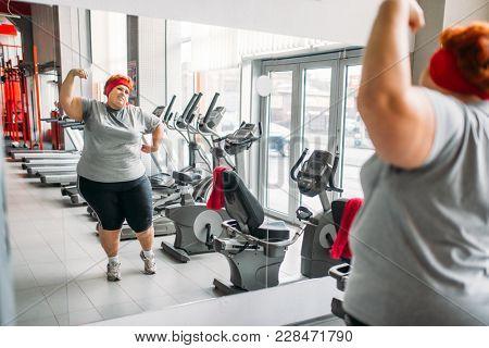 Fat sweaty woman training against mirror in gym