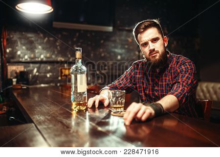 Alcoholic sitting at bar and drinks strong alcohol