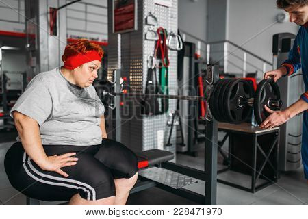 Overweight sweaty woman on workout with barbell