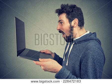 Side View Of Extremely Amazed Hipster Man Watching Laptop With New Upgrade.