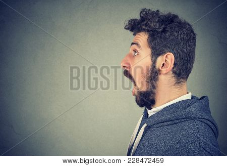Side View Of Man Showing Face Expression Of Astonishment With Mouth Opened Looking Away.