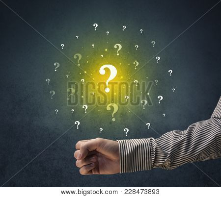 Yellow question marks hovering over young hand