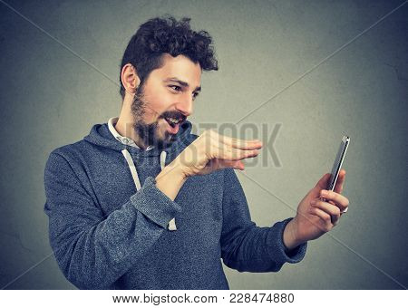 Young Expressive Man Manipulating With Gadget Using Magic And Standing On Gray Background.