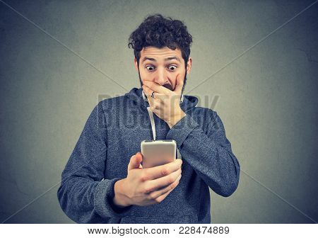 Young Man Looking Shocked While Watching Breaking News On Phone.