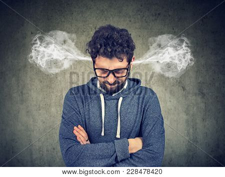 Angry Young Man, Blowing Steam Coming Out Of Ears, About To Have Nervous Breakdown Isolated On Gray