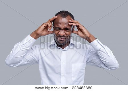 Terrible Headache. Attractive Unhappy Dark-eyed Afro-american Man Wearing A White Shirt And Touching