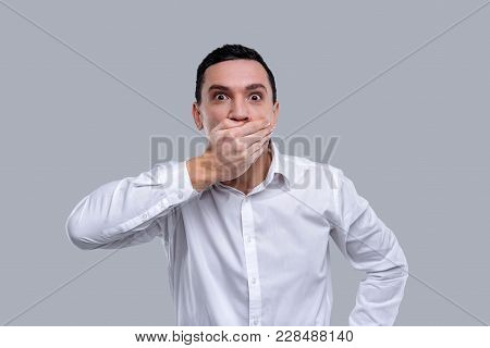 I Am Amazed. Handsome Surprised Dark-eyed Young Man Wearing A White Shirt And Closing His Mouth With