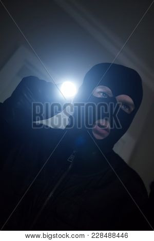 Thief Wearing Mask With A Flashlight In The House.