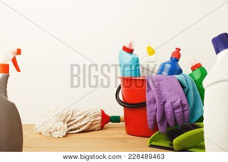 Variety Of House Cleaning Products On Wood Table, Close Up. Bucket, Rubber Gloves, Mop, Disinfection