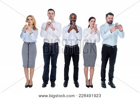 Addicted. Attractive Young Successful Addicted Colleagues Standing In One Line And Using Their Phone