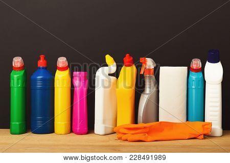 Group Of Colorful Cleaning Products On Dark Background. Different Bottles And Rubber Gloves On Wood