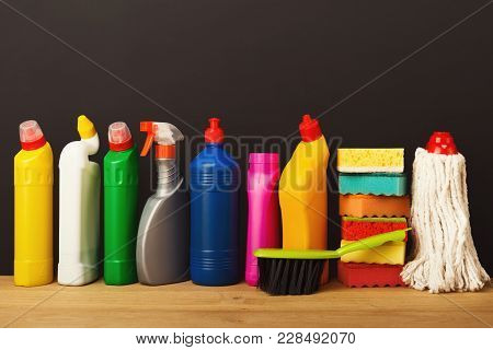 Group Of Colorful Cleaning Products On Dark Background. Different Bottles, Sponges And Brush On Wood