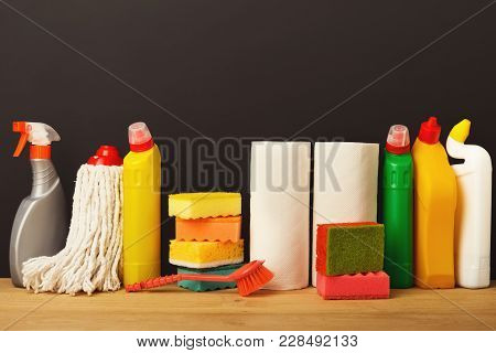Group Of Colorful Cleaning Products On Dark Background. Different Bottles, Sponges, Brush And Mop On