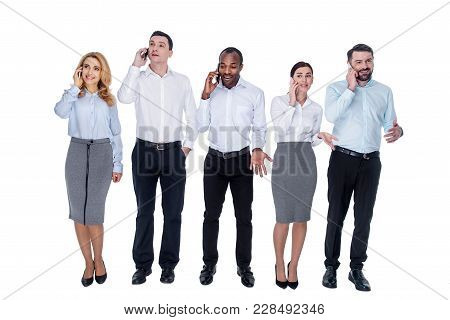Discussing Work. Good-looking Cheerful Young Successful Colleagues Standing In One Line And Talking