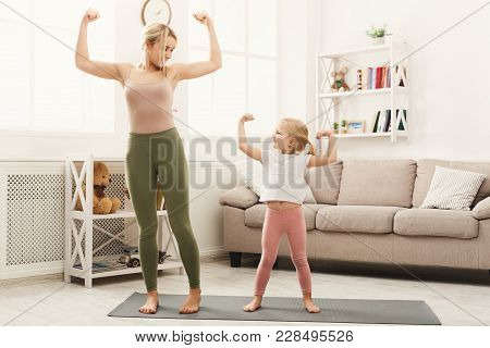 Young Mother Showing Her Little Daughter Exercises. Happy Girls Training At Home. Motherhood And Spo