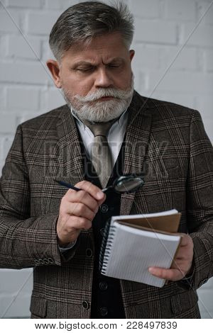 Senior Man In Tweed Suit Reading Notes In Notebook With Magnifying Glass
