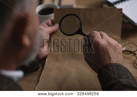 Close-up Shot Of Senior Man Reading Letter With Magnifying Glass