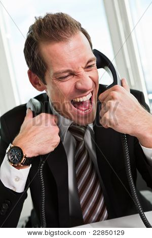 Stressed businessman screaming on the phone