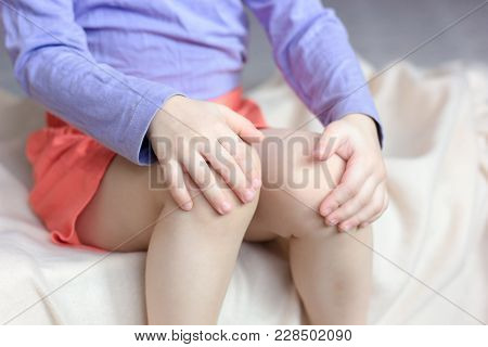 Little Kid Girl Feel Hurt And Pain, She Holds Her Knees