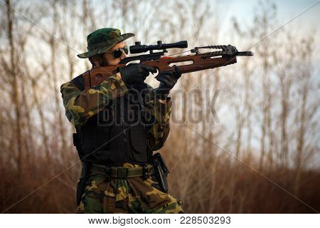 The Military Man Is Shooting With Crossbow Weapon Outdoors.