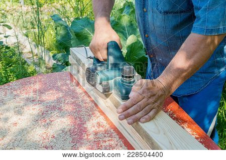 The Master Sharpens The Wooden Panel With An Electric Sander On A Sunny Day In The Garden. Danger. V
