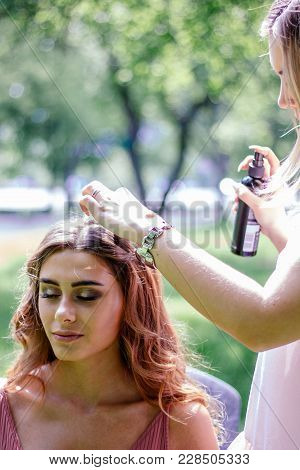 Stylist Spraying Hairs Of Young Girl With Hair Spray