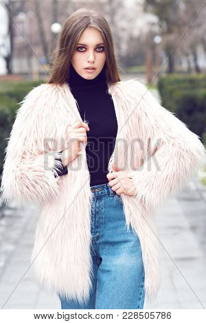 The Girl In A Pink Fur Coat Fashion. On The Street There Is Snow. Gloomy Makeup. Fashionable Woman.