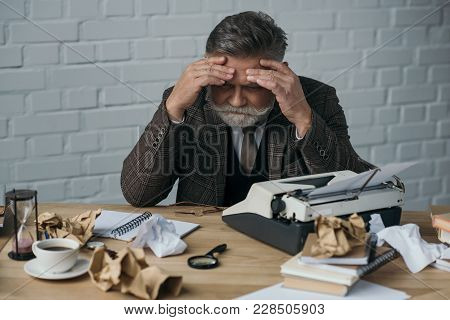 Depressed Senior Writer Sitting At His Messy Workplace And Holding Head With Hands