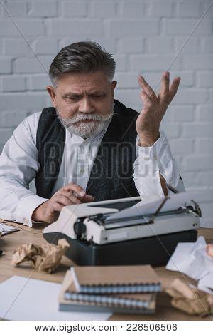 Depressed Senior Writer Trying To Work With Typewriter At Messy Workplace
