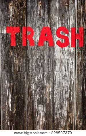 The Word 'trash' Painted In Red On A Rustic Wooden Background