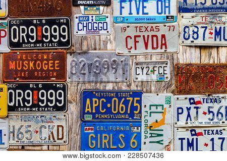 Luckenbach, Tx - January 11, 2018 - Various Old License Plates Displayed On A Wooden Wall.