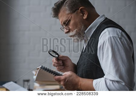 Handsome Senior Man Reading Notes In Notebook With Magnifying Glass