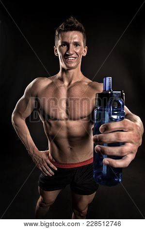 Thirst, Dehydration, Drinking Water Concept. Sportsman With Sport Bottle On Dark Background. Man Ath