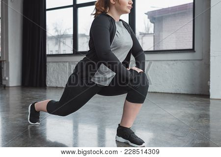 view of Curvy girl in gym stretching legs poster