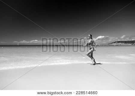 Woman In Sexy Swimsuit Running On Beach With White Sand, Turquoise Sea Or Ocean And Blue Sky On Sunn