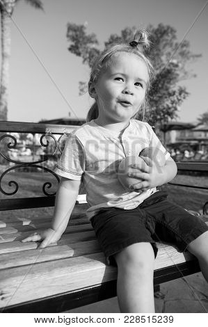 Child Or Small Little Boy Sitting With Two Oranges On Bench On Sunny Day In Park. Cute Kid With Blon